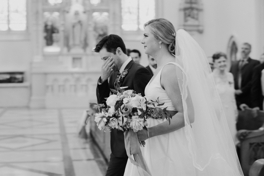 black and white photo of groom wiping his eyes as he walks up to the altar with his bride