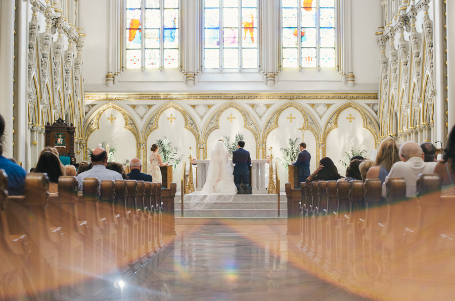 bride and groom kneeing at the altar of st joseph cathedral