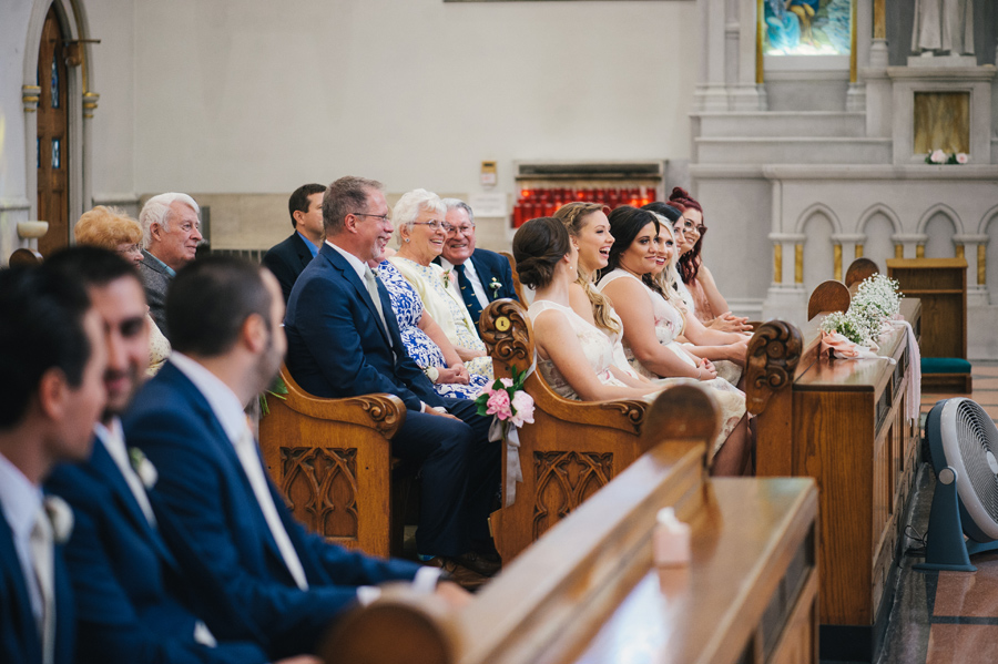 wedding guests and bridal party laughing in the pews