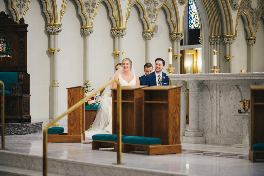 bride and groom laughing at the altar