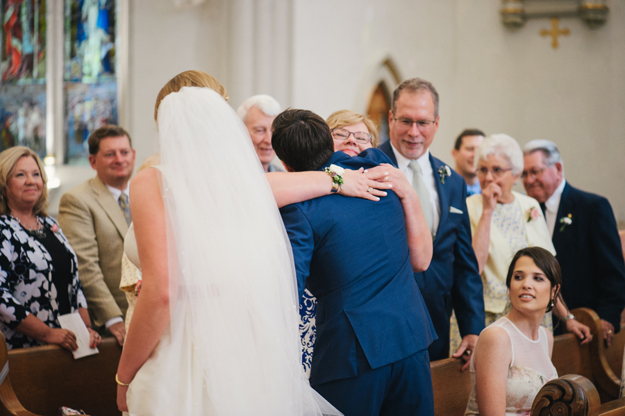 groom hugging the brides mother at the church