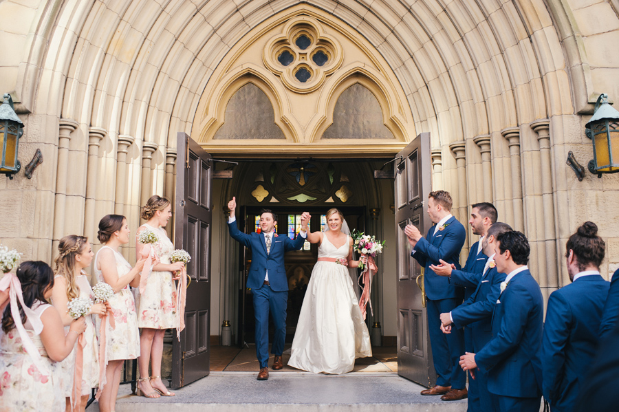 bride and groom exiting the church to cheers of the wedding party