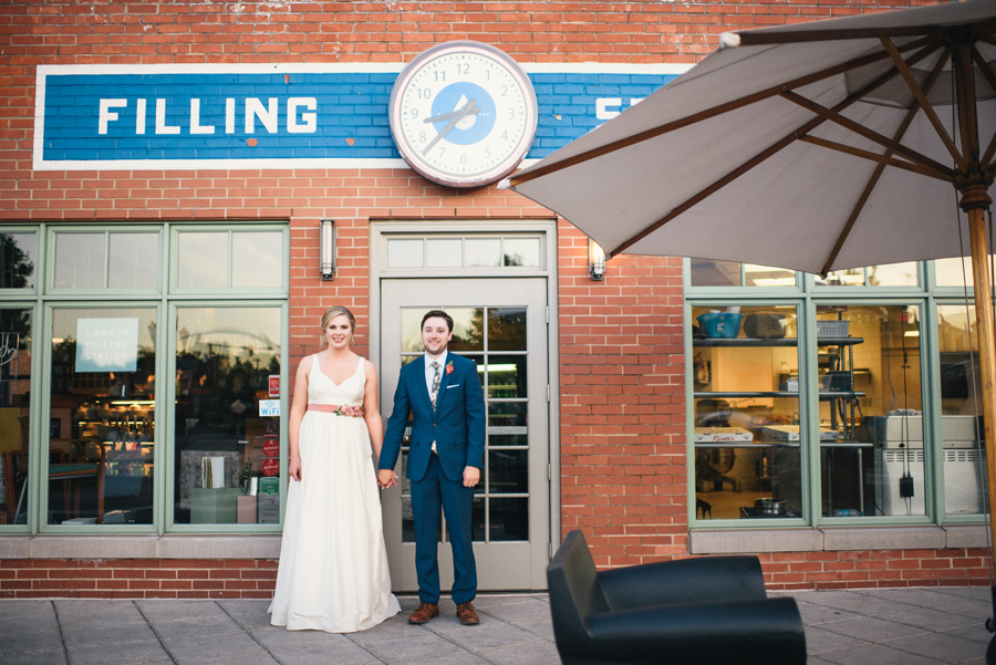 bride and groom holding hands in front of larkinville