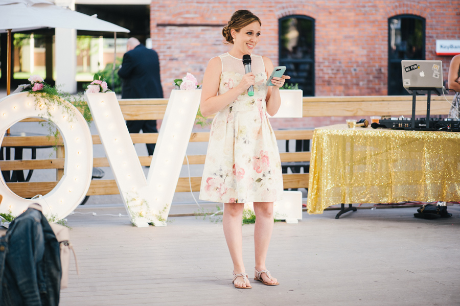 maid of honor reading speech off her phone at reception