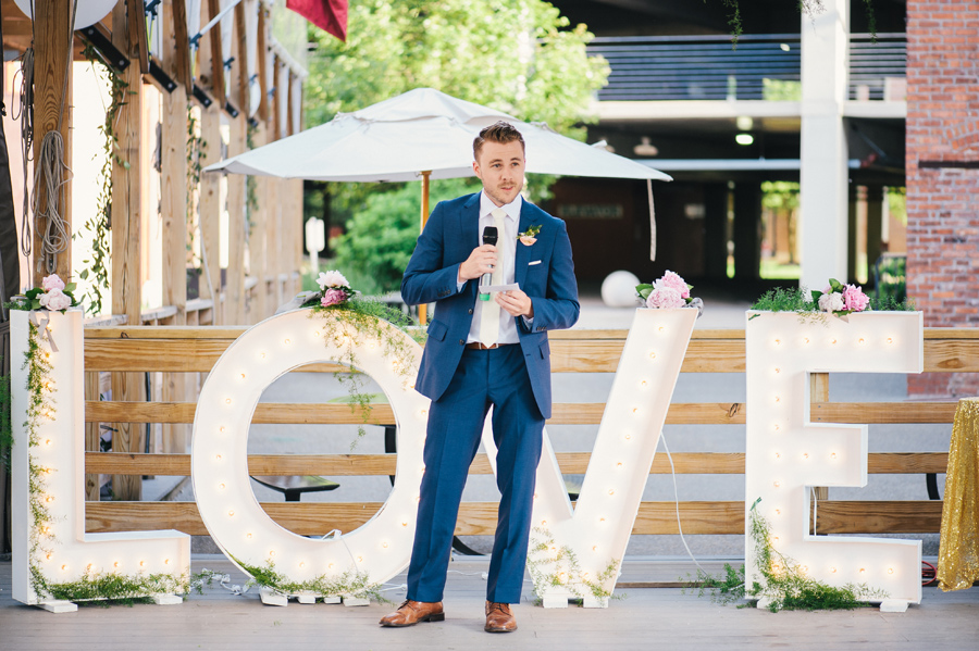 best man delivering his speech in front of giant love marquee letters