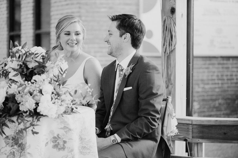 black and white photo of bride and groom smiling during speeches