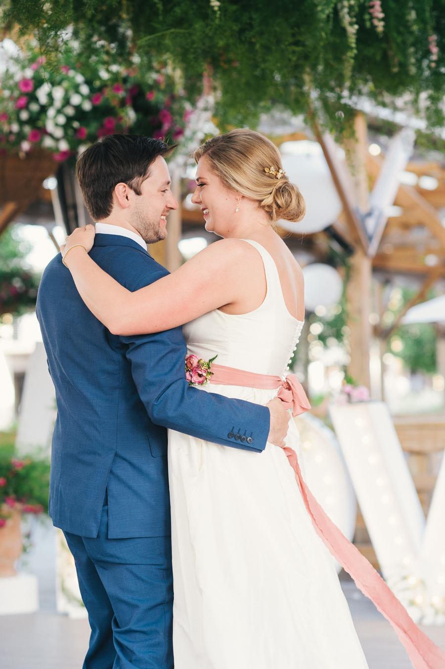 bride and groom's first dance under greenery canopy