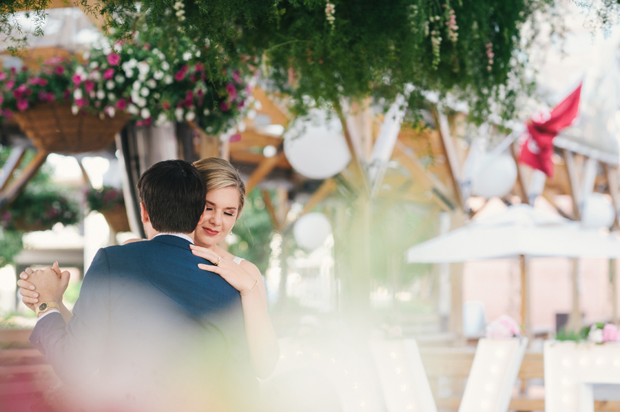 bride and groom slow dancing surrounded by flowers and greenery
