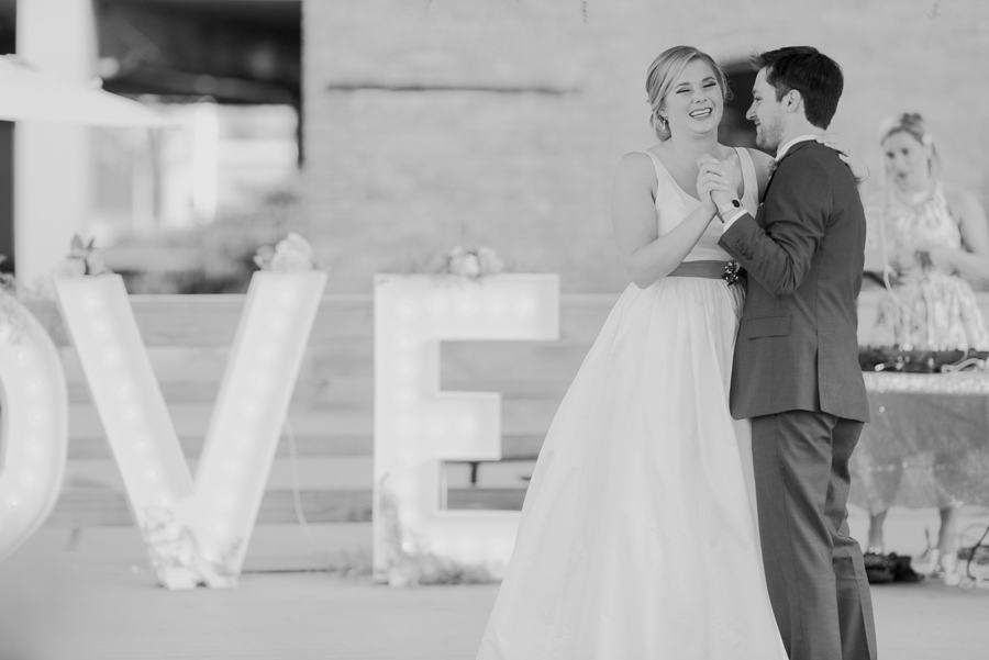 black and white photo of bride laughing during the first dance