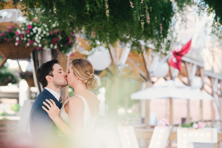 bride and groom kissing underneath the greenery chandelier