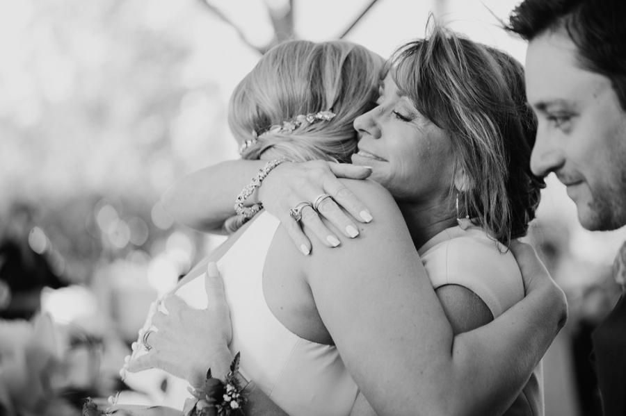 black and white photo of groom's mother hugging the bride