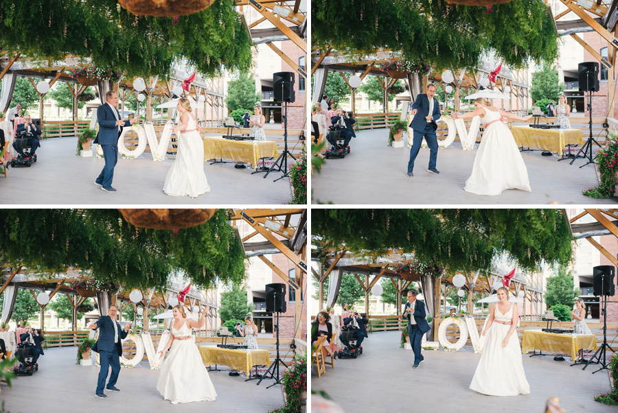 bride and her father having fun dancing together under greenery canopy