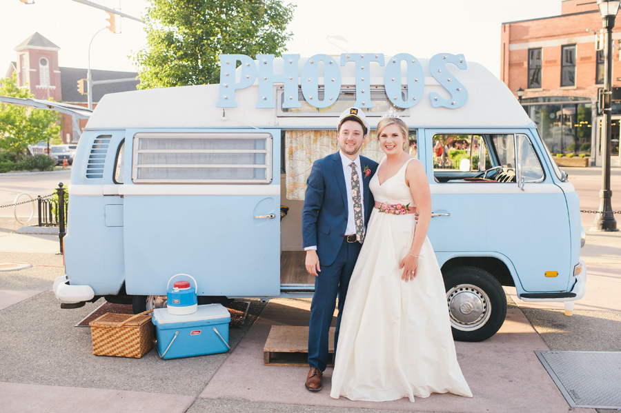 bride and groom standing in front of buffalove bus photo booth