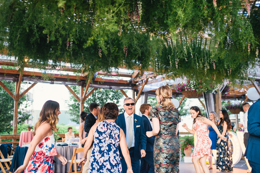 wedding guests dancing under greenery chandelier made by west wind floral