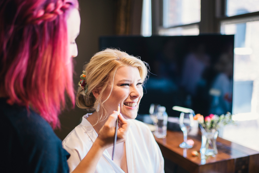 bride smiling while getting her makeup done by rachel rizzo