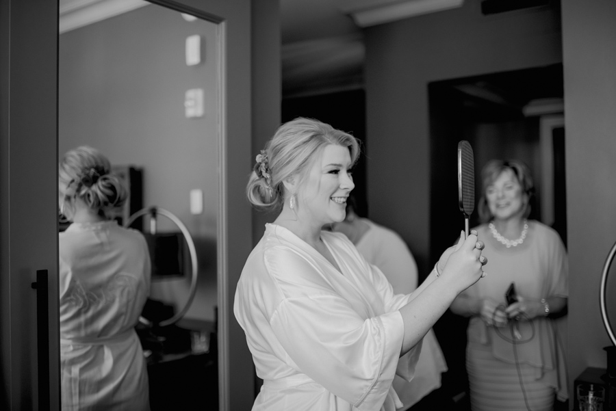 black and white of bride looking at her updo in the mirror