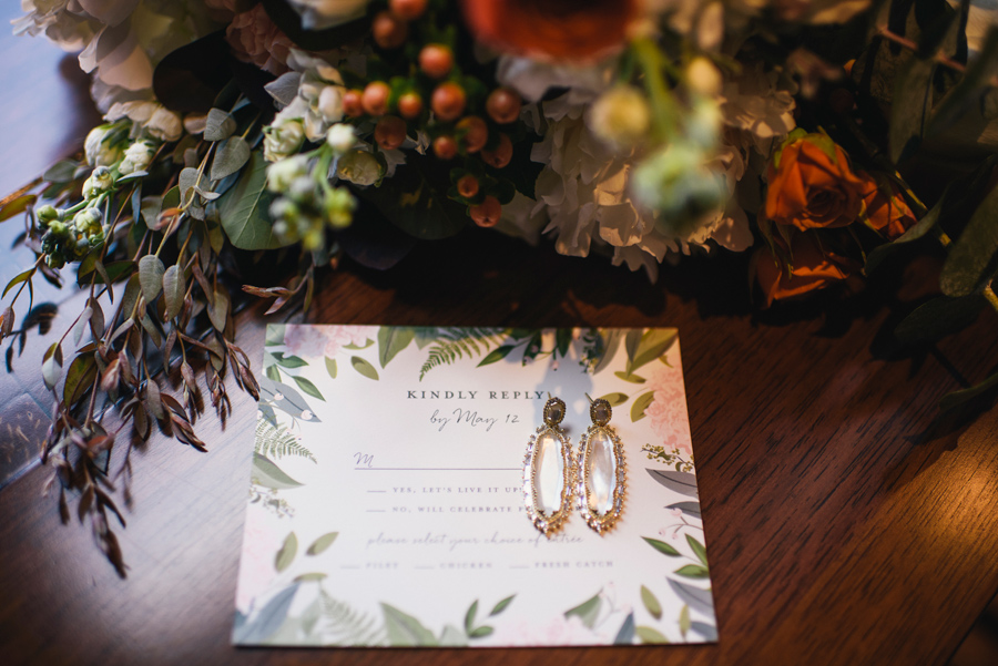 rsvp card with bride's earrings and bouquet