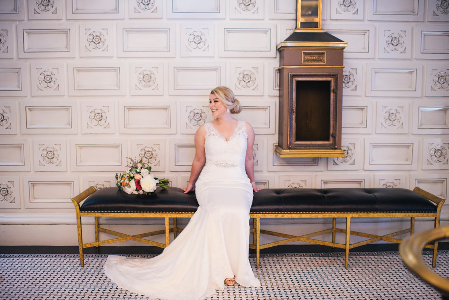 bride posing on a bench in the lobby of the curtiss hotel