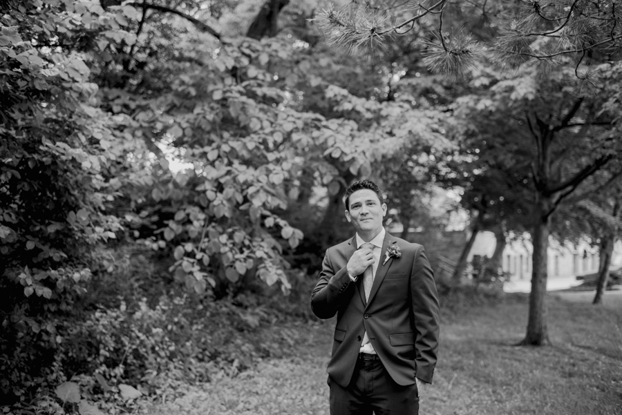 black and white portrait of groom adjusting his tie in the park