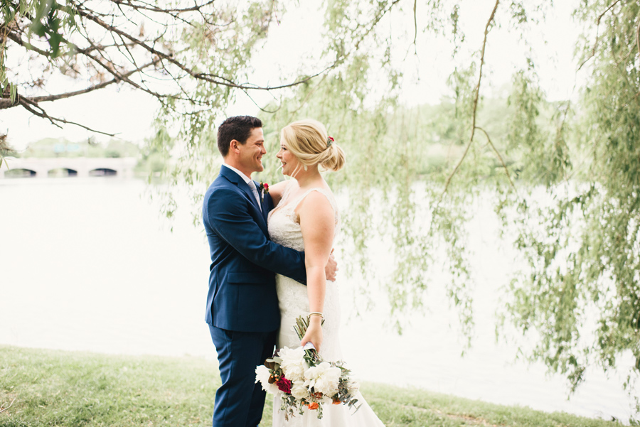 bride and groom smiling at each other next to hoyt lake