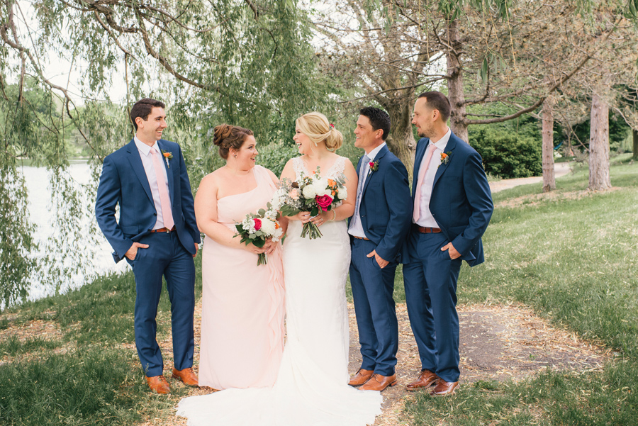 wedding party laughing together under a willow tree