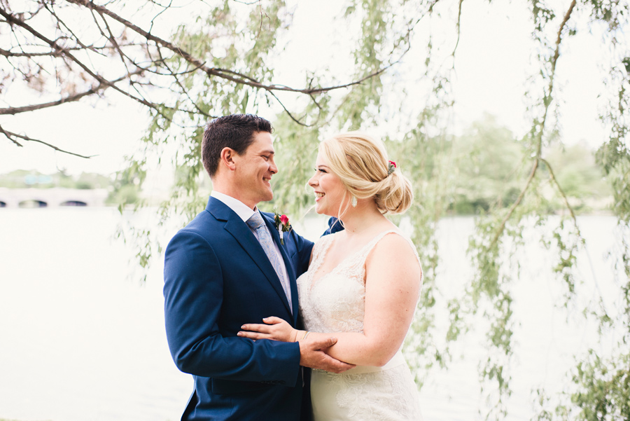 bride and groom smiling together under a willow tree