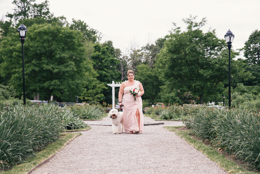 maid of honor walking down the aisle with bride and groom's dog