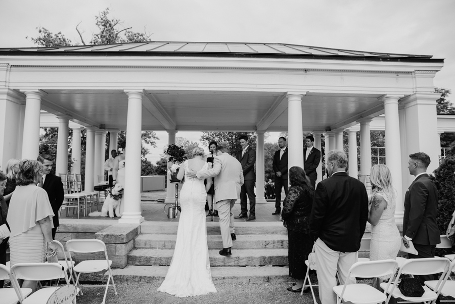 black and white of father of the bride helping her up the steps at the ceremony