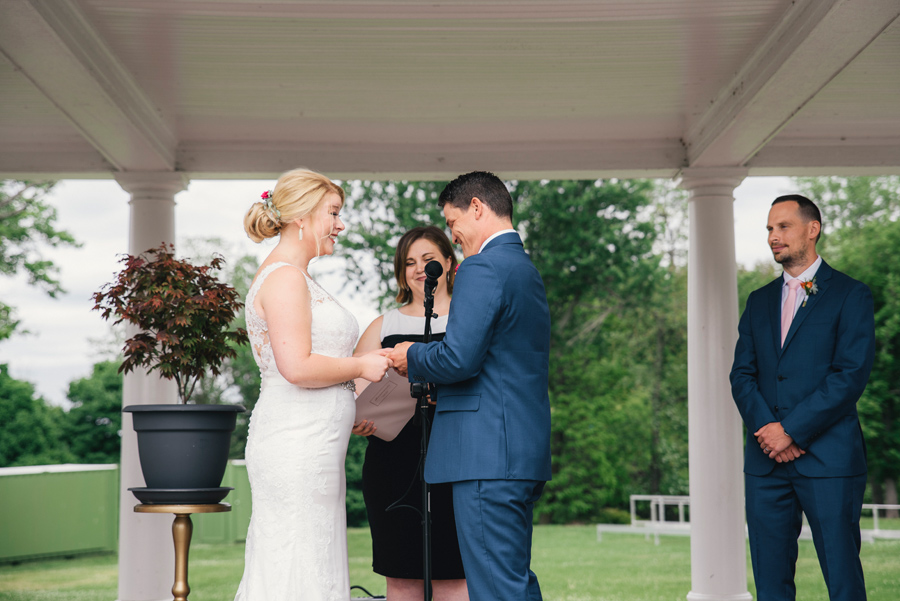 bride and groom exchanging rings at delaware park rose garden