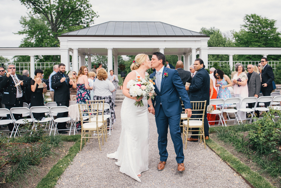 bride and groom kissing at the end of the aisle at delaware park rose garden