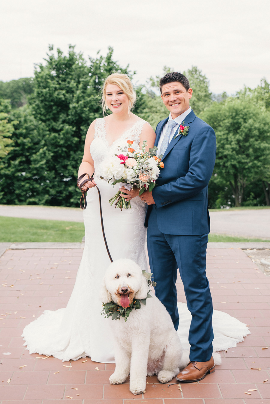 bride and groom posing with their dog at delaware park