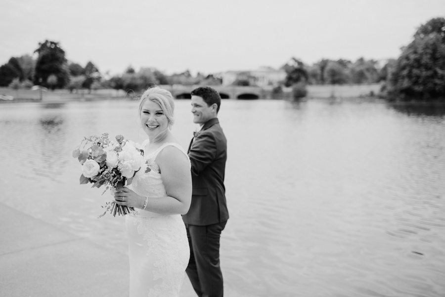 black and white of bride smiling at the camera with groom