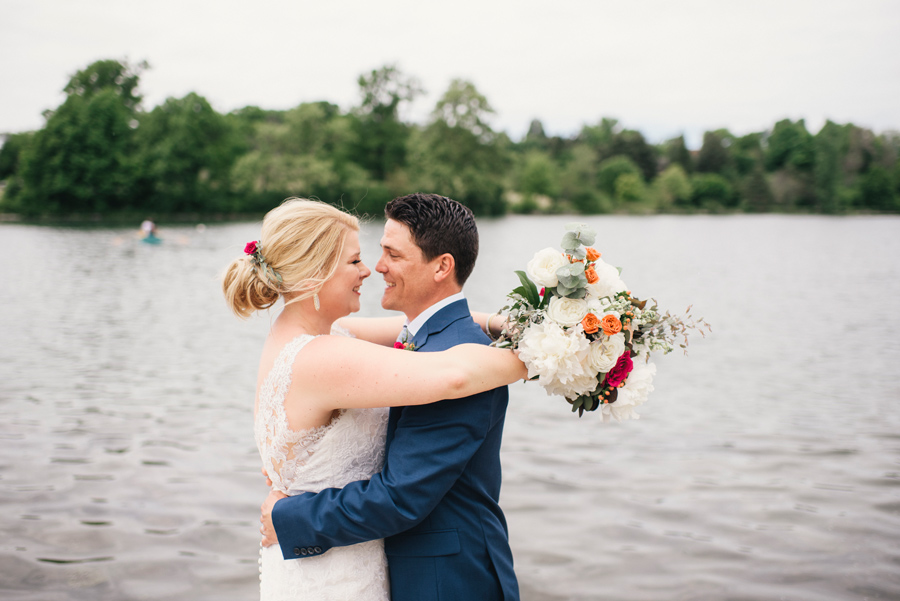 bride and groom smiling at each other in front of hoyt lake