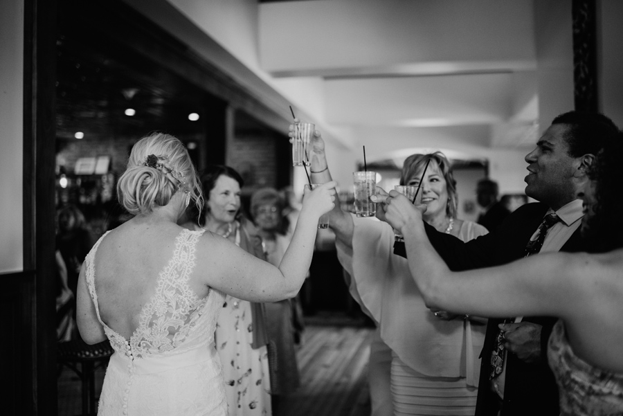 bride and wedding guests toasting each other at cocktail hour