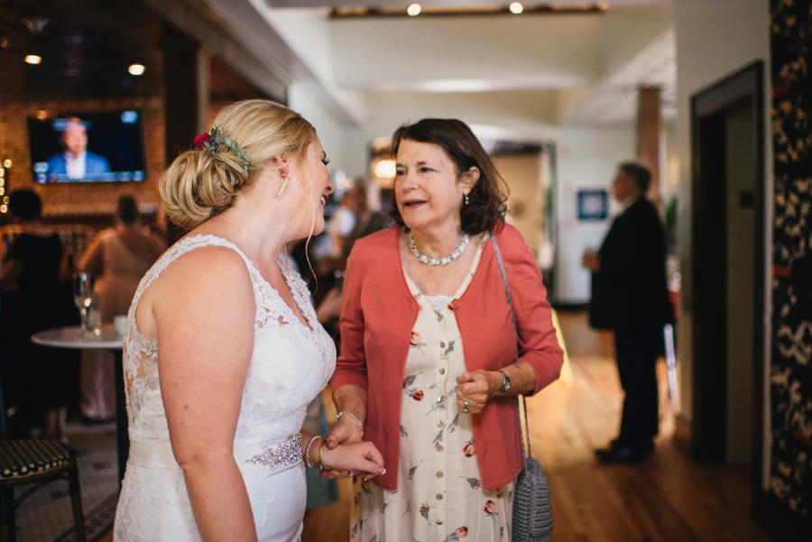 bride chatting with a wedding guest during cocktail hour