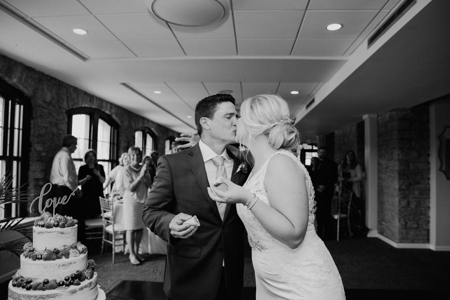 black and white of bride and groom kissing in front of cake