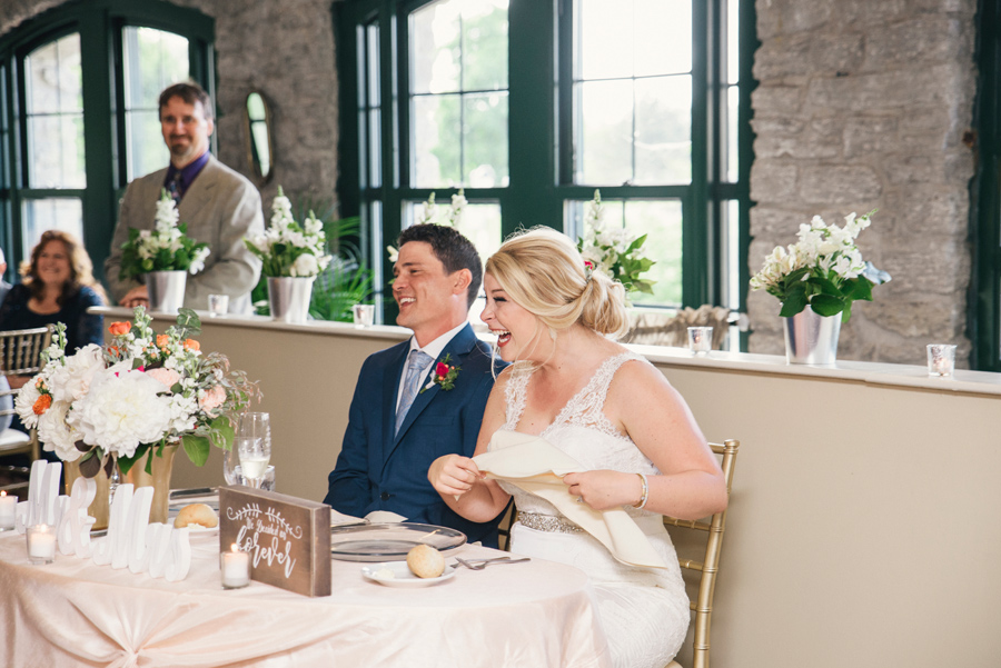 bride and groom laughing during mad of honor speech