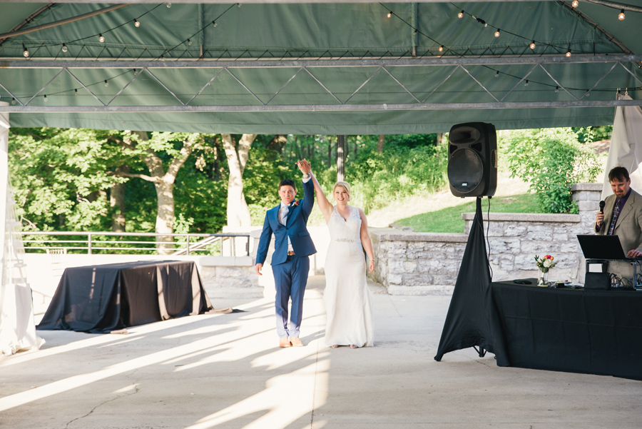 bride and groom enter outdoor tented patio for first dance