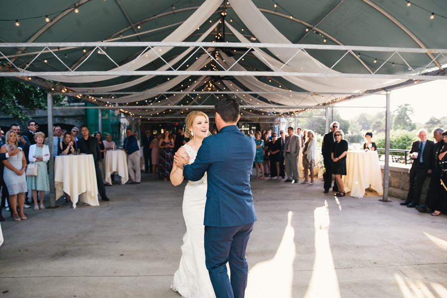 bride and groom dancing together under tent