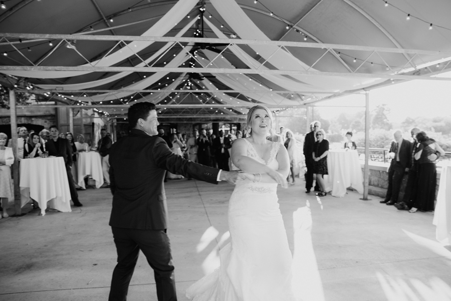 black and white of groom twirling bride during first dance