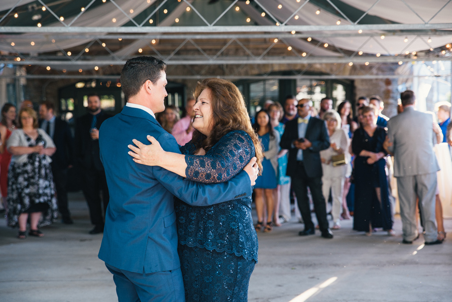 mother of the groom and her son smiling on the dance floor