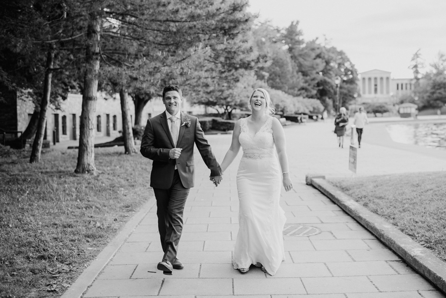 black and white of bride and groom walking together along hoyt lake