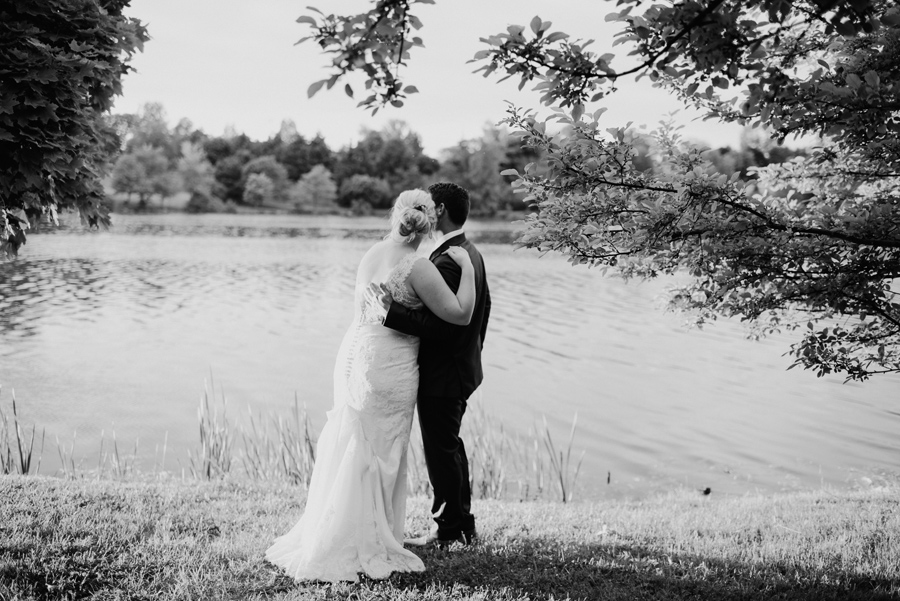 black and white of bride and groom hugging and gazing at the lake together