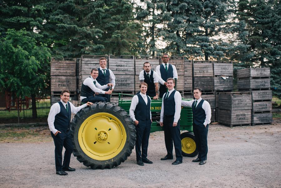groom and groomsmen posing with restored 1941 john deere tractor