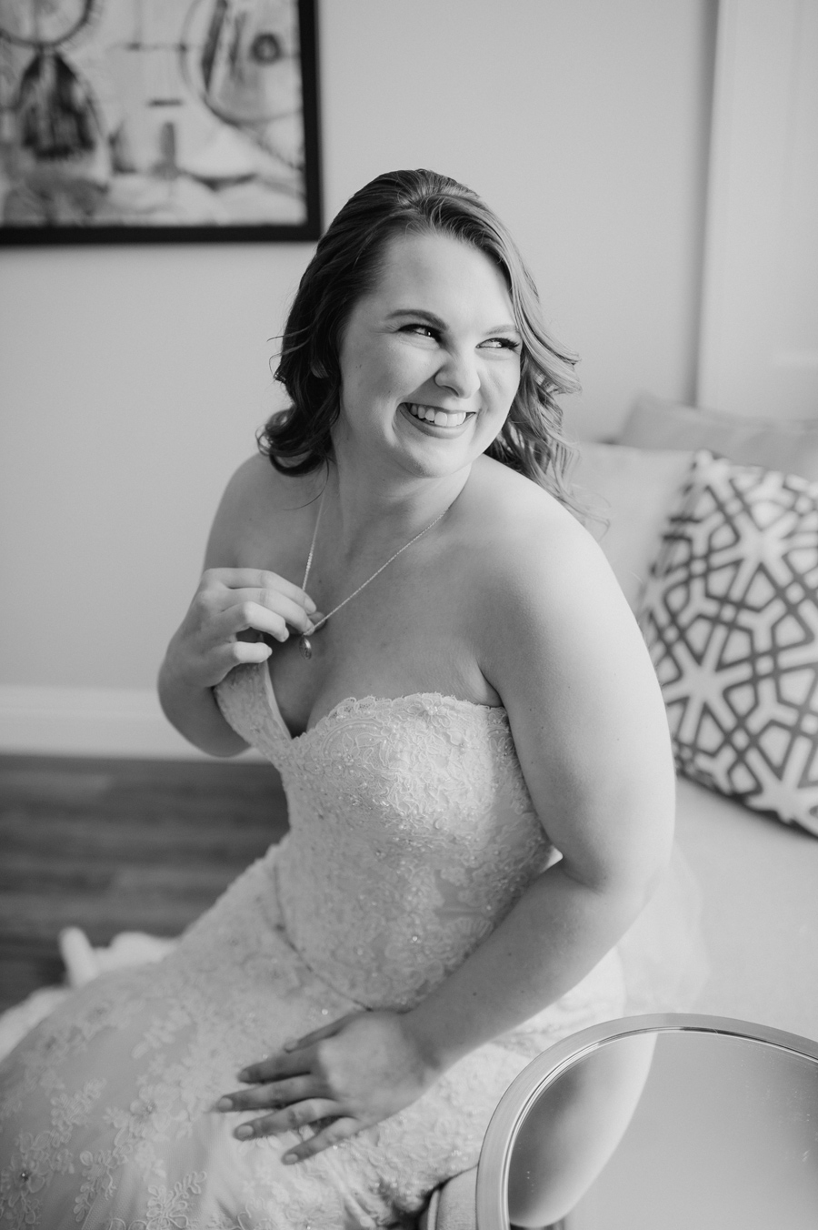black and white photo of the bride smiling and holding the locket around her neck