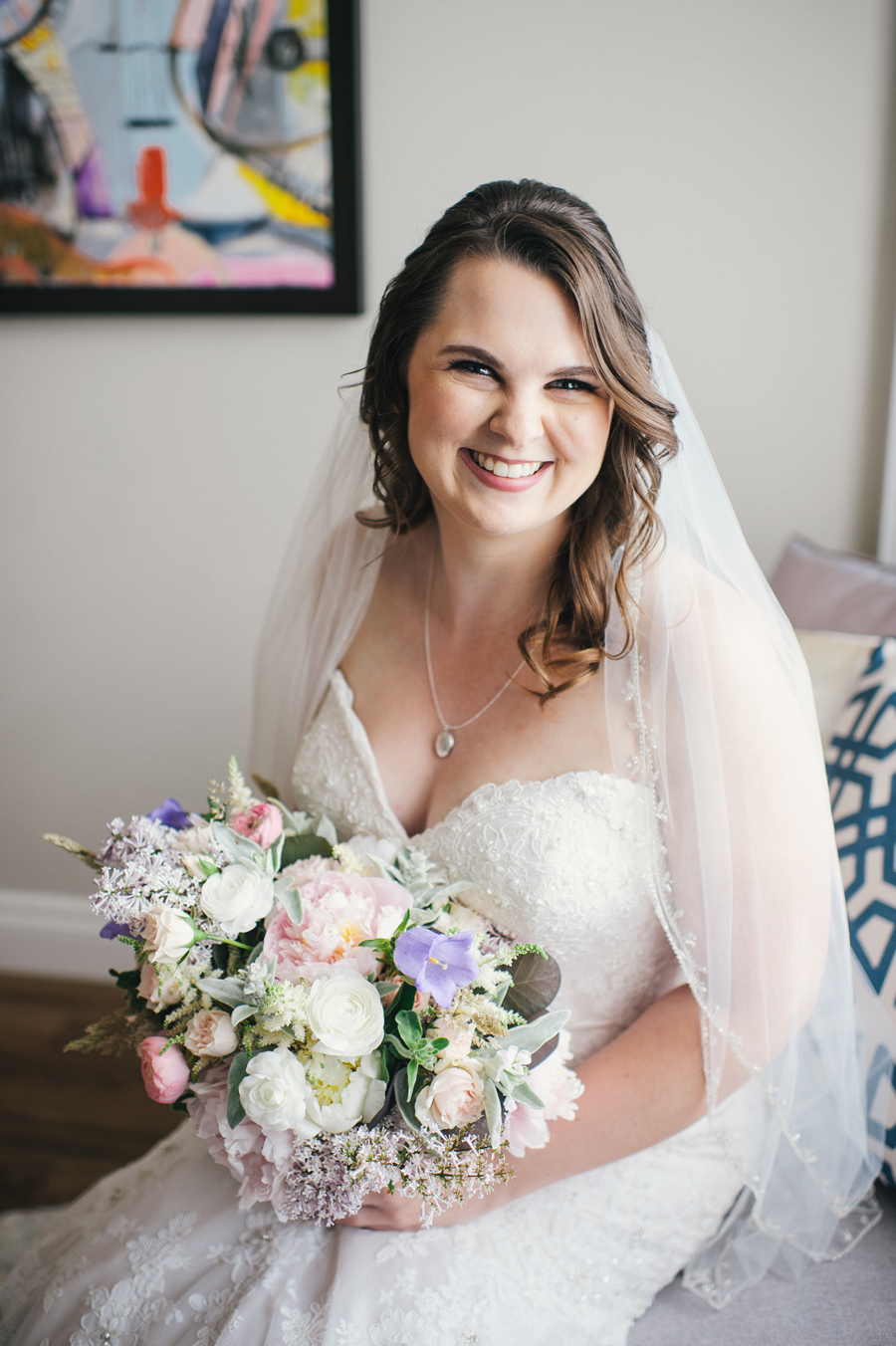 portrait of bride with her veil on and holding bouquet