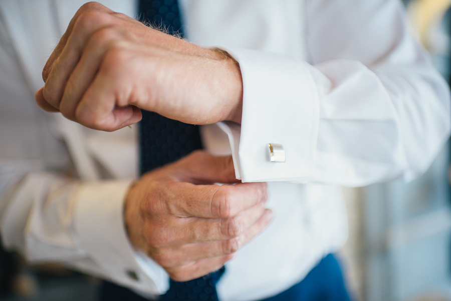 groom adjusting his cuff link