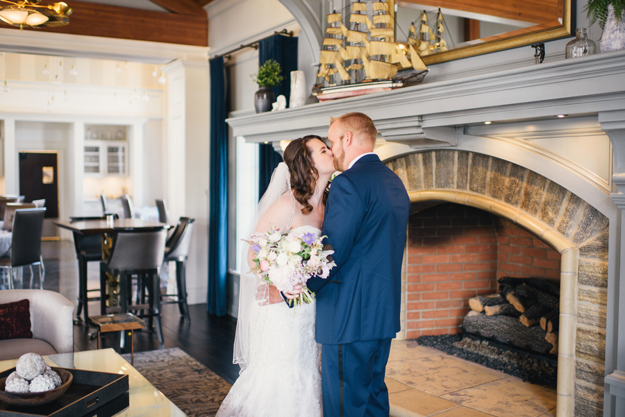 bride and groom kissing in front of fireplace mantel
