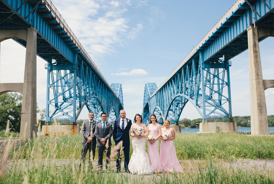 wedding party posing under the grand island bridge