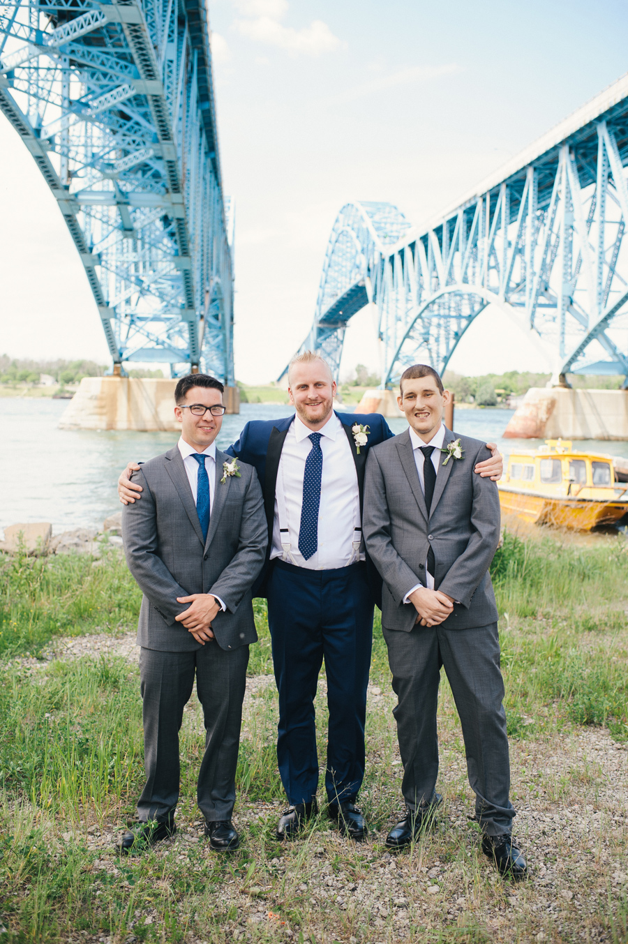groom and groomsmen posing under the grand island bridge